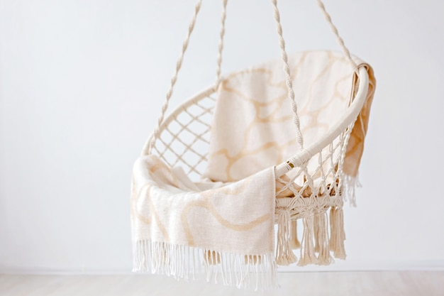 Hangende rotan stoel met beige plaid in het huis