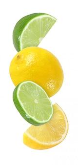 Hangende, vallende, vliegende stuk limoen en citroen fruit geïsoleerd op een witte achtergrond met uitknippad