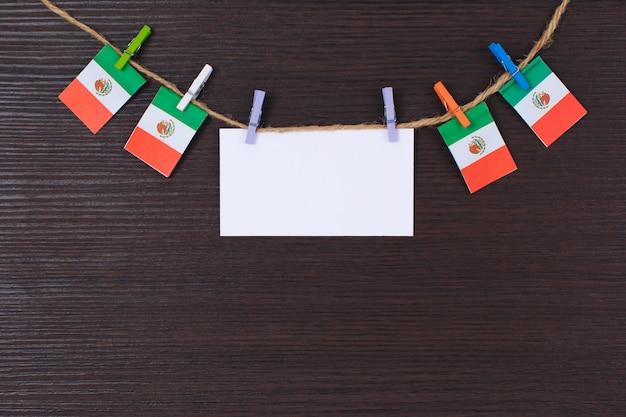 Hangende vlaggen van mexico in bijlage aan kabel met wasknijpers met copyspace op wit notadocument