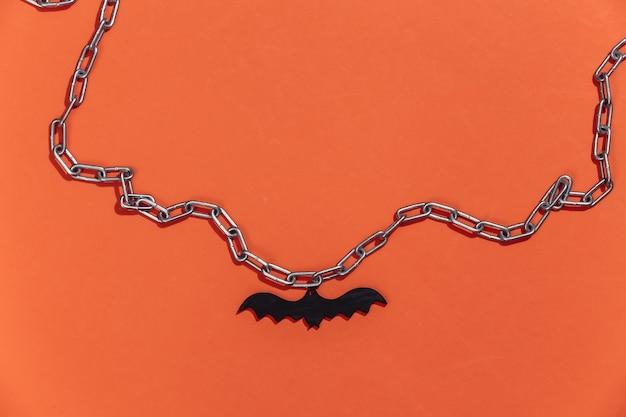 Hanger van een vleermuis aan een ketting. fel oranje achtergrond
