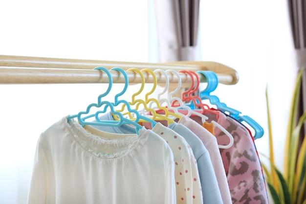 Hangers met kleding hangen in huis aan een houten rek
