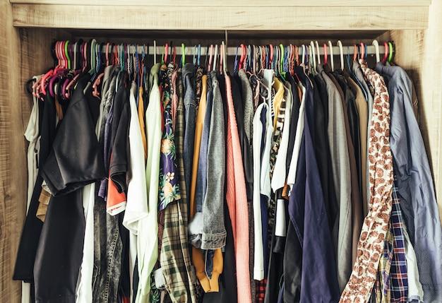 Hangers met verschillende kleding in garderobekast