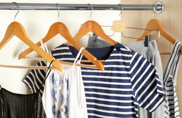 Hangers met verschillende kleren in garderobekast