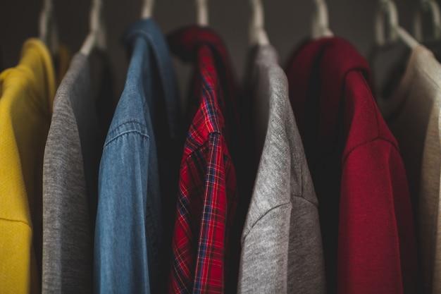 Hangers met verschillende vrijetijdskleding in de kast van de huisgarderobe