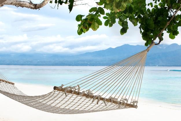Hangmat hangend tussen bomen op een zandstrand en achtergrond van azuurblauwe bali kust van het eiland gili trawangan