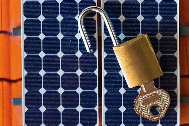 Hangslot met sleutel op fotovoltaïsch zonnepaneel op zwart