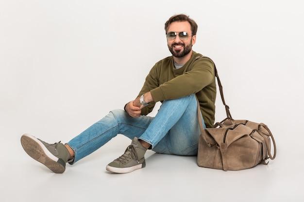 Hansome bebaarde stijlvolle man zittend op de vloer geïsoleerd gekleed in sweatshirt met reistas, spijkerbroek en zonnebril dragen