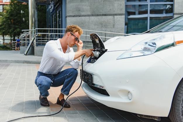 Hansome man zit in de buurt van zijn nieuwe moderne elektrische auto en houdt de stekker van de oplader vast, terwijl de auto wordt opgeladen bij het laadstation
