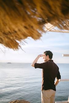 Hansome mens die en ver in kust in zwart overhemd overdag kijkt kijkt.