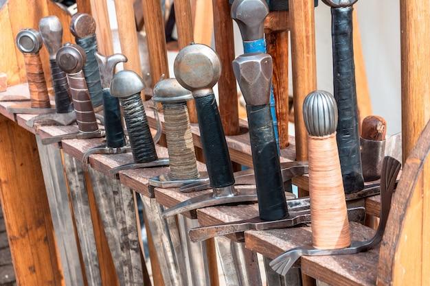 Hanteert zwaarden uit de oudheid op een rij.