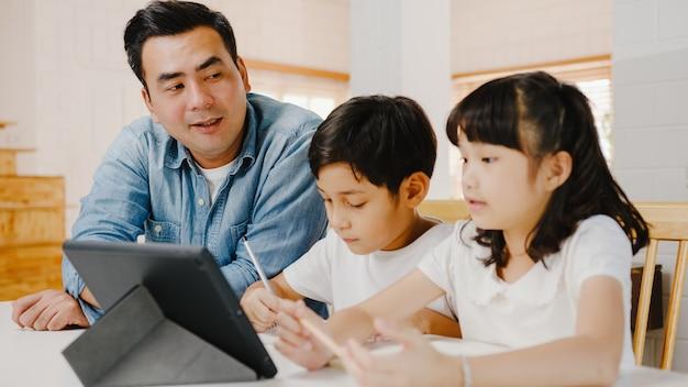 Happy asia family homeschooling, vader leert kinderen thuis met behulp van digitale tablet in de woonkamer.