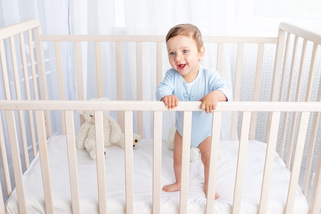 Happy baby boy staat in de wieg in de kinderkamer en lacht of lacht