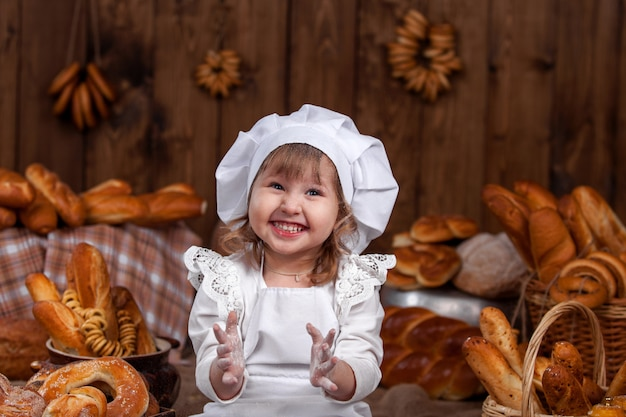 Happy baby chef, in bloem, lachen, klappen, chef spelen, bakkerij, veel brood