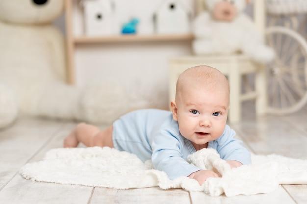 Happy baby ligt thuis in de kinderkamer met speelgoed, ontwikkelingsconcept en spelletjes
