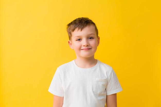 Happy babyjongen van 7 jaar in een wit t-shirt op een gele achtergrond