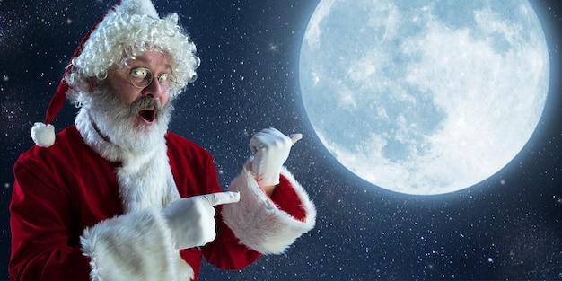 Happy christmas santa claus voor middernacht maan. kaukasisch mannelijk model in het kostuum van de traditionele vakantie. concept van vakantie, nieuwjaar, winterstemming, geschenken. verkoop. wijzend naar de zijkant.