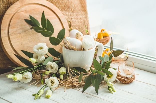 Happy easter achtergrond. paasei in een nest met bloemendecoratie dichtbij het venster. kwarteleitjes. vrolijk pasen concept
