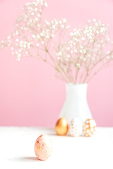 Happy easter achtergrond. roze en gouden ei en wit bloeiende gipskruid op roze achtergrond. teder gezellig stilleven.