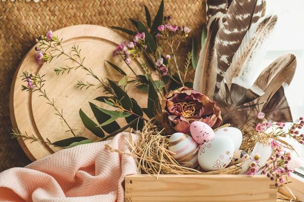 Happy easter achtergrond. roze paaseieren in een nest met florale decoraties en veren in de buurt van het venster