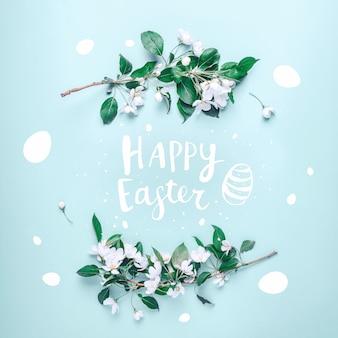 Happy easter belettering in een frame van de bloemen van een appelboom op een pastelblauw