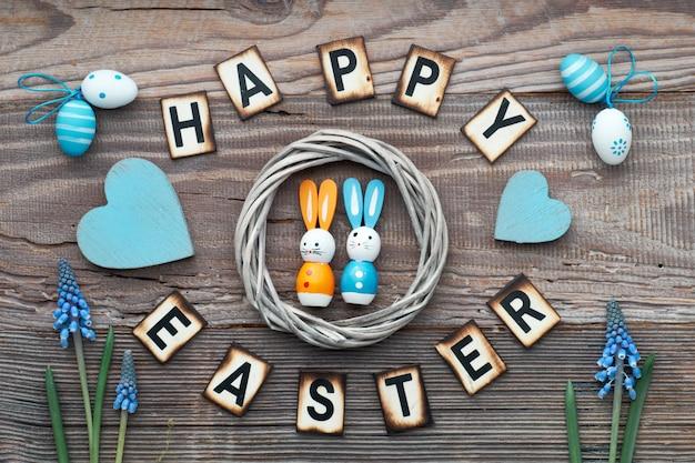 Happy easter belettering tekst op rustiek hout met lentebloemen, paaseieren, houten hart en decoraties