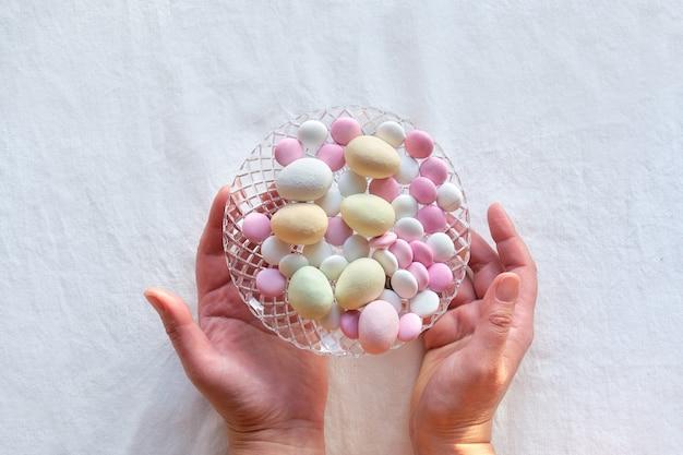 Happy easter hands toont kristallen glazen vaas met marsepeinen paaseieren en chocoladeknoopjes.