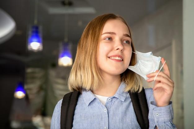 Happy girl-student doet een beschermend medisch masker af. portret van blonde vrouwelijke student aan de universiteit aan het einde van de coronavirus covid lockdown. nieuw normaal veilig leven na ziek. quarantaine is voorbij.