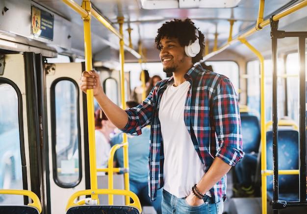 Happy glimlachte afro-amerikaan stond in een bus en luisterde naar de muziek via zijn telefoon.