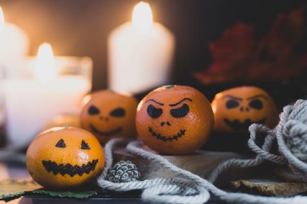 Happy halloween-citrus, mandarijnen beschilderd met enge, grappige gezichten. donkere foto met kaarsen. alternatieven voor traditionele halloween-pompoenen.