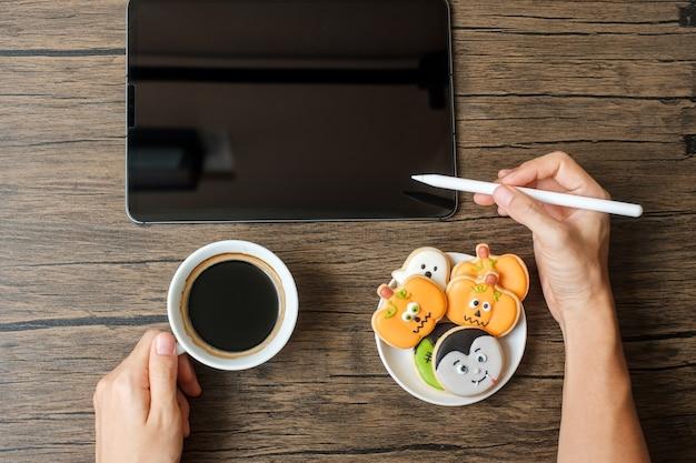 Happy halloween-dag met cookie, koffie en tablet. online winkelen, hallo oktober, herfstherfst, feestelijk, feest- en vakantieconcept