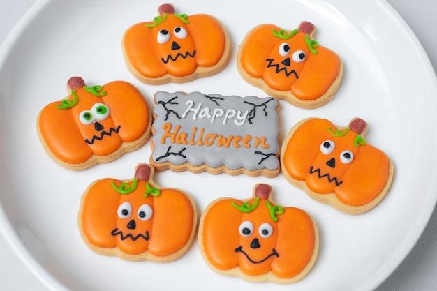 Happy halloween-dag met grappige koekjes, verschillende pompoenkoekjes op plaat. trick or threat, hallo oktober, herfst herfst, traditioneel, feest- en vakantieconcept