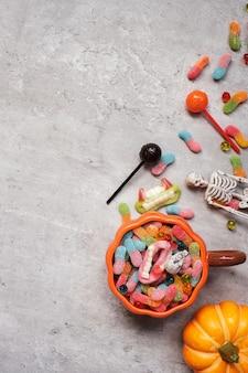 Happy halloween-dag met spooksuikergoed, pompoen, kom en decoratief. trick or threat, hallo oktober, herfstherfst, feestelijk, feest- en vakantieconcept