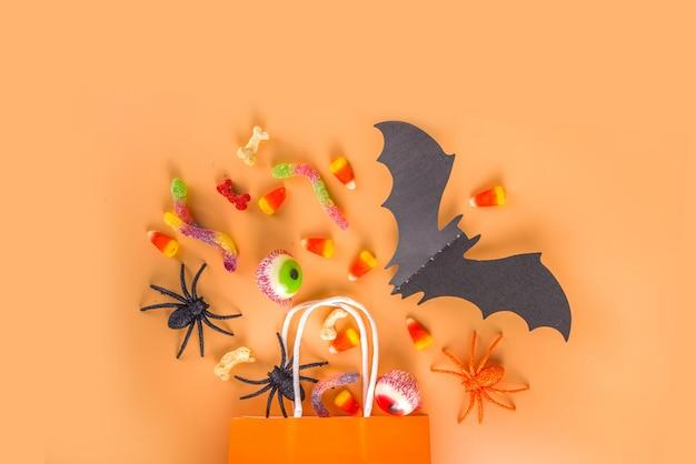 Happy halloween dag vakantie achtergrond. plat lag met snoep en decoraties voor kinderfeestje, emmerpakket met spinnen, snoepsnoepjes, vleermuis, op kleurrijk oranje papier kopieerruimte bovenaanzicht