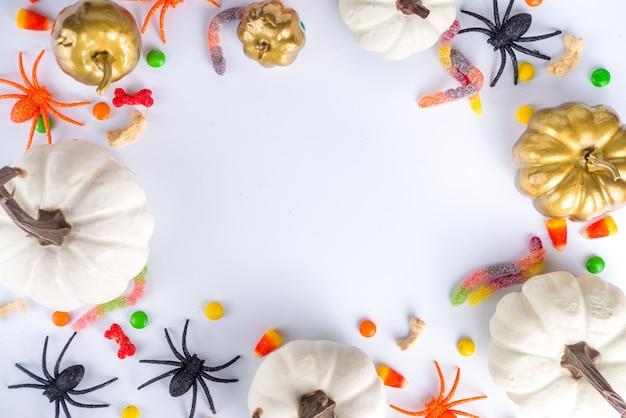 Happy halloween dag vakantie achtergrond. plat lag met snoep en decoraties voor kinderfeestje, emmerpakket met spinnen, snoepsnoepjes, vleermuis, op witte tafel kopieerruimte bovenaanzicht frame