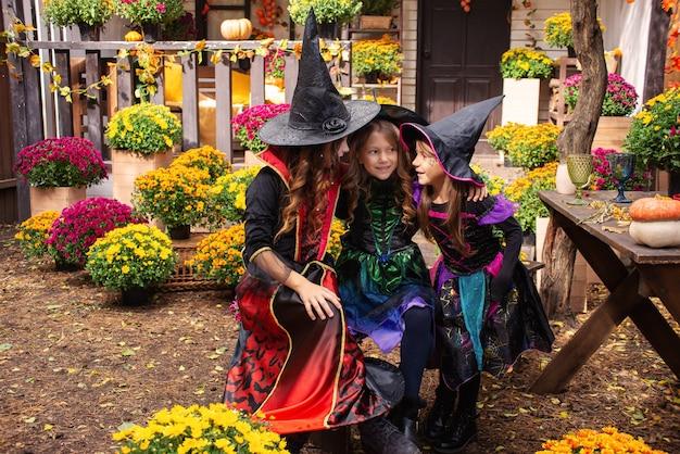 Happy halloween drie schattige lachende meisjes in heksenkostuums vieren halloween
