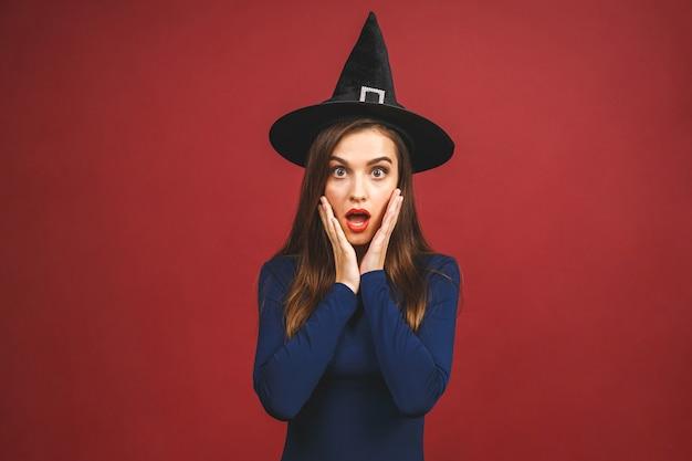 Happy halloween heks met lichte make-up en lang haar. het mooie jonge verraste vrouw stellen in heksen sexy kostuum. geïsoleerd op rode achtergrond.