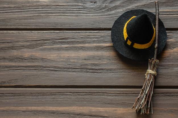 Happy halloween vakantie achtergrond met heks accessoires hoed en bezem op houten tafel