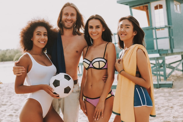 Happy hipster man en beach football girls team
