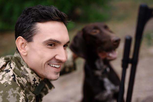 Happy hunter in camouflage huisdierenvriendelijke hond.