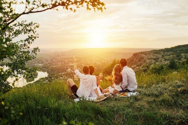 Happy jonge vrienden met picknick op de berg. ze zijn allemaal blij, hebben plezier, lachen, drinken wijn en genieten van een prachtige zonsondergang en landschap.