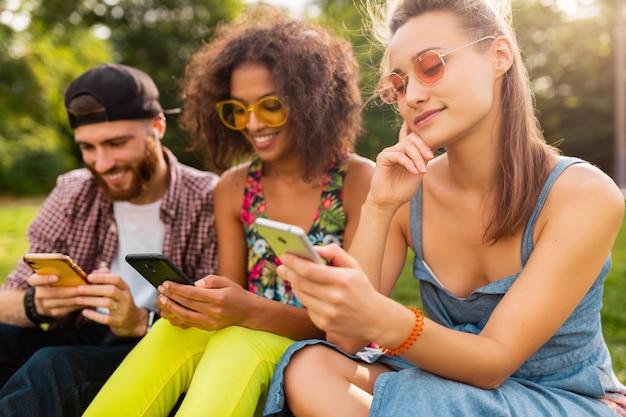 Happy jonge vrienden zitten park met behulp van smartphones