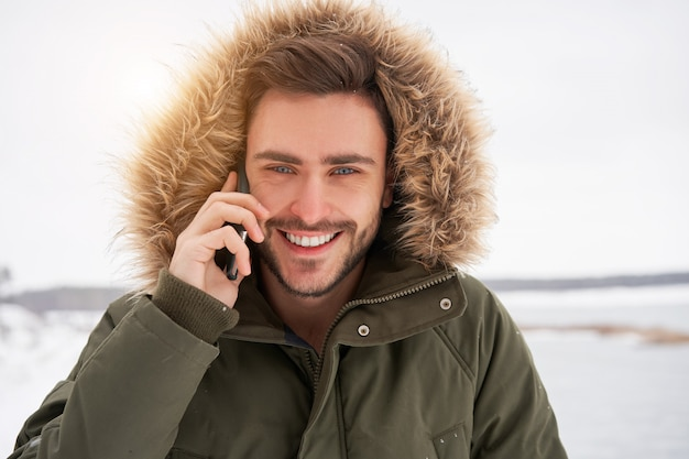 Happy lachende jonge blanke man praten over de telefoon winter