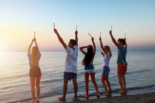 Happy lachende vrienden lopen op het strand met fonkelende kaarsen in de hand