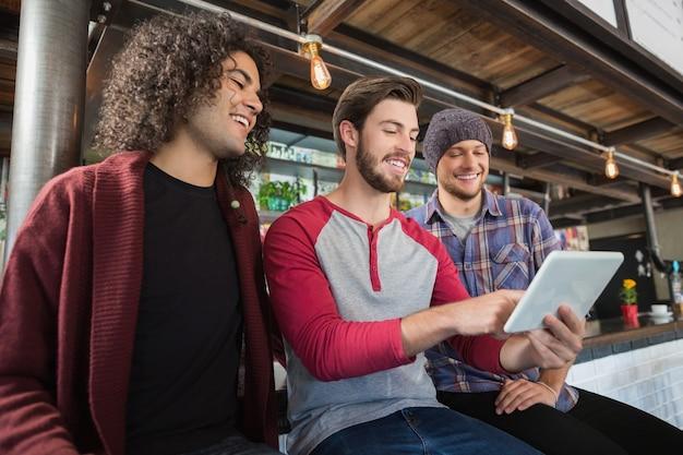 Happy mannelijke vrienden met behulp van digitale tablet in restaurant