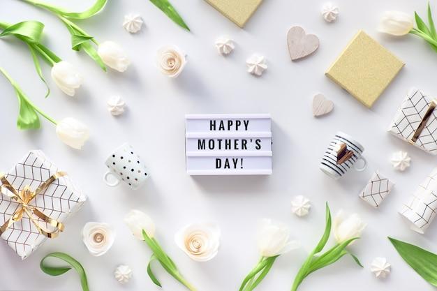 Happy mother's day tekst op lightbox. plat lag op moederdag, bedankt mam! witte plat lag, verse tulpenbloemen, koffiekopjes, geschenk verpakt in geometrisch gouden papier en snoepjes.