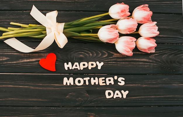 Happy mothers day inscriptie met tulpen boeket op tafel