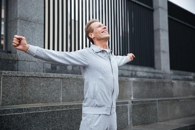 Happy runner in grijze sportkleding en koptelefoon opwarmen op straat met de handen opzij.