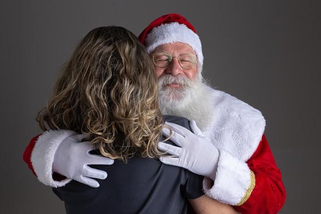 Happy santa claus knuffelen vrouw, dankbaarheid en liefde op kerstnacht.