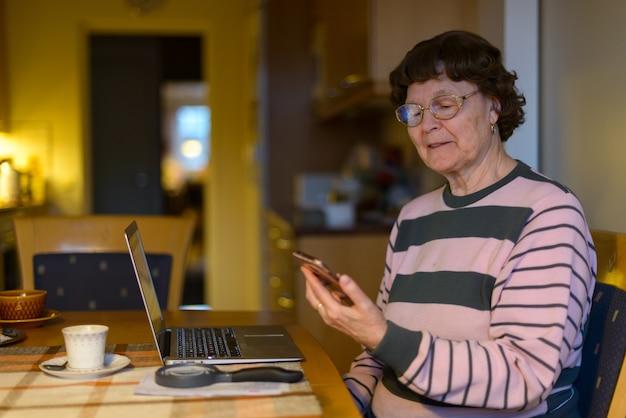 Happy senior vrouw lachend terwijl mobiele telefoon