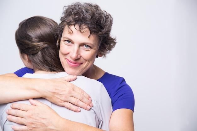 Happy senior vrouw omarmen jonge volwassen dochter